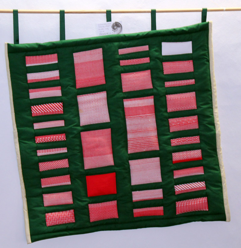 Ein Quilt, zusammengesetzt aus fehlerhaftem Material, mit fehlerhafter Verarbeitung und schiefer Aufhängung. Rot, weiß und grün. Steht zum Verkauf.
