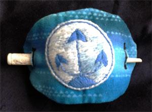 Haarspange mit Efferdsymbol, DMC-Baumwollgarn auf Patchworkstoff. Gestickt freihand nach Bildvorlage.